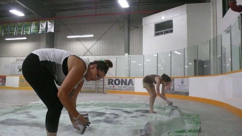 volunteers making an indoor lake for art show